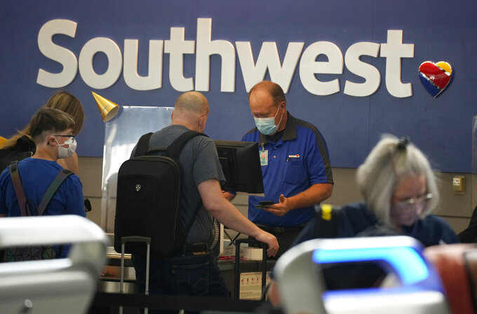 FILE - In this Wednesday, June 16, 2021, file photo, Southwest Airlines ticketing agent helps a traveller at the check-in counter at Denver International Airport in Denver.  Southwest Airlines turned a profit in June without assistance from the U.S., which the company is calling a milestone in it's recovery from the pandemic. The Dallas company said Thursday, July 22 it had profit of 57 cents per share. (AP Photo/David Zalubowski, File)