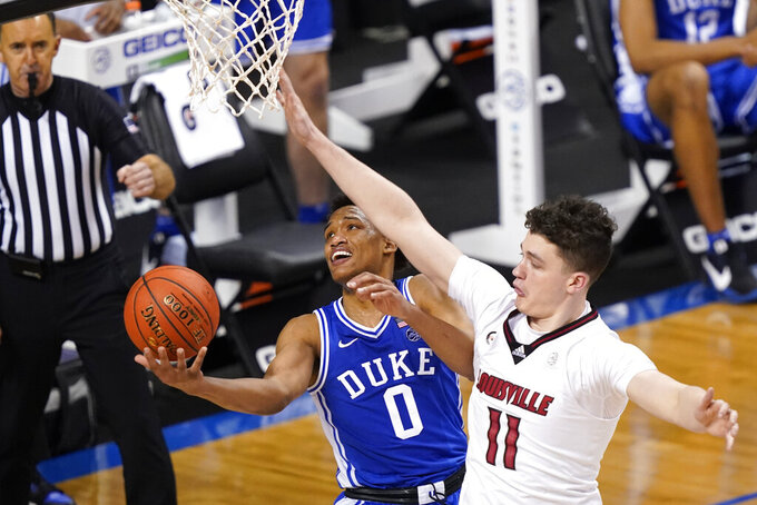 Duke forward Wendell Moore Jr. (0) goes up for a shot as Louisville forward Quinn Slazinski (11) defends during the second half of an NCAA college basketball game in the second round of the Atlantic Coast Conference tournament in Greensboro, N.C., Wednesday, March 10, 2021. (AP Photo/Gerry Broome)