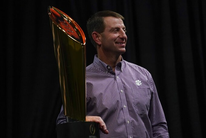 Clemson head coach Dabo Swinney poses with the championship trophy at a news conference for the NCAA college football playoff championship game Tuesday, Jan. 8, 2019, in San Jose, Calif. (AP Photo/Morry Gash)