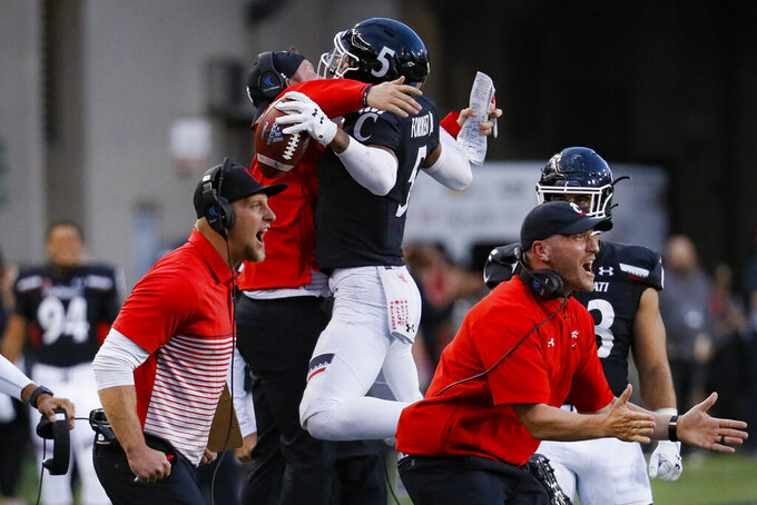 Cincinnati safety Darrick Forrest (5) celebrates his interception with a team coach during the second half of an NCAA college football game against Tulsa, Saturday, Oct. 19, 2019, in Cincinnati. (AP Photo/John Minchillo)