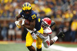 Michigan running back Hassan Haskins (25) tries to break the tackle of Rutgers linebacker Drew Singleton (11) in the first half of an NCAA college football game in Ann Arbor, Mich., Saturday, Sept. 28, 2019. (AP Photo/Paul Sancya)