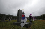 South Korean national flags are placed near the gravestones of soldiers who died during the 1950-1953 Korean War at the National Cemetery in Seoul, South Korea, Thursday, June 25, 2020. North and South Korea on Thursday marked the 70th anniversary of the start of the Korean War with largely subdued commemorations amid the coronavirus pandemic, a day after the North abruptly halted a pressure campaign against the South. (AP Photo/Lee Jin-man)