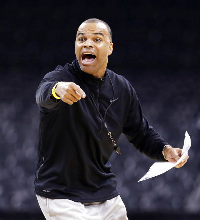 FILE - In this March 19, 2014, file photo, Harvard head coach Tommy Amaker directs his team during practice for the NCAA college basketball tournament in Spokane, Wash. When George Floyd died this spring under a policeman's knee, Amaker didn't send out a tweet affirming Black Lives Matter or add a uniform patch calling for Equality. He simply continued exposing his players to social justice issues, as he had been doing for more than a decade, establishing the program as a model for other teams only now showing an interest. (AP Photo/Elaine Thompson, File)