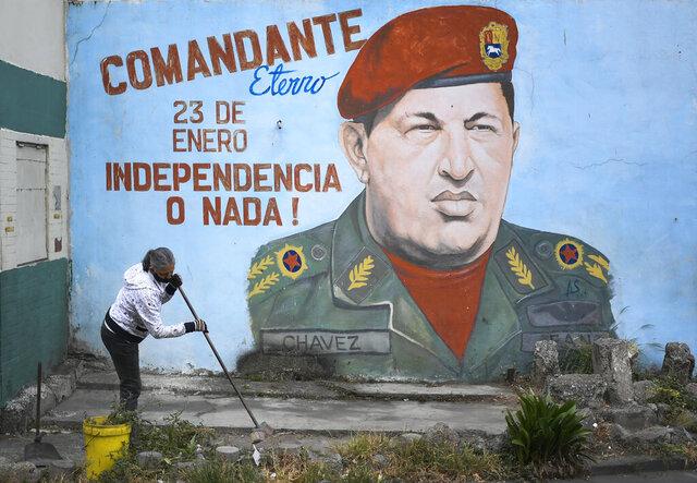 Una mujer porta una mascarilla mientras limpia una acera frente a un mural del fallecido presidente venezolano Hugo Chávez durante una jornada de limpieza y desinfección organizada por el consejo comunal y organización colectiva del vecindario 23 de Enero de Caracas, Venezuela, el miércoles 29 de abril de 2020. (AP Foto/Matias Delacroix)