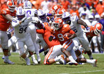 Clemson's Travis Etienne rushes out of the backfield while pursued by Furman's Jaylan Reid, 75, and Jonah Tibbs during the first half of an NCAA college football game Saturday, Sept. 1, 2018, in Clemson, S.C. (AP Photo/Richard Shiro)