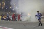 Staff extinguish flames from Haas driver Romain Grosjean of France's car after a crash during the Formula One race in Bahrain International Circuit in Sakhir, Bahrain, Sunday, Nov. 29, 2020. (Tolga Bozoglu, Pool via AP)