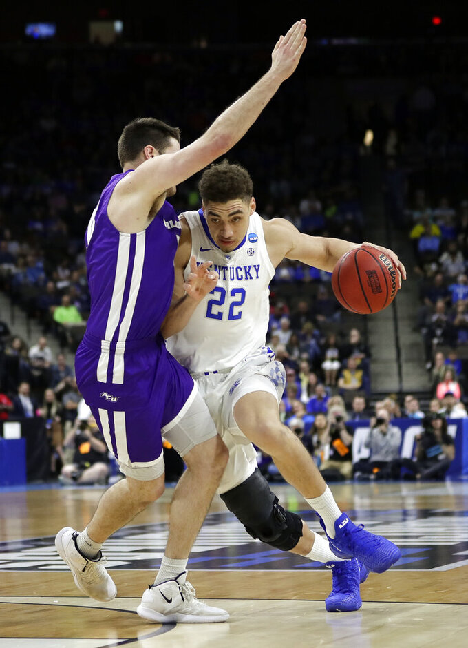Kentucky's Reid Travis (22) drives around Abilene Christian's Hayden Farquhar during the first half of a first-round game in the NCAA men's college basketball tournament in Jacksonville, Fla. Thursday, March 21, 2019. (AP Photo/John Raoux)