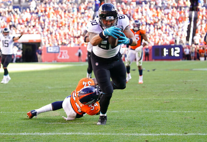 Jacksonville Jaguars tight end James O'Shaughnessy scores a touchdown as Denver Broncos strong safety Will Parks defends during the second half of an NFL football game Sunday, Sept. 29, 2019, in Denver. (AP Photo/Jack Dempsey)