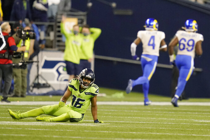 Seattle Seahawks wide receiver Tyler Lockett, left, sits on the turf after he got tripped up and had a pass intended for him intercepted by Los Angeles Rams safety Nick Scott (not shown) during the second half of an NFL football game, Thursday, Oct. 7, 2021, in Seattle. The Rams won 26-17. (AP Photo/Elaine Thompson)
