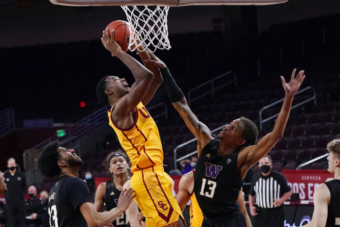 Southern California forward Evan Mobley, center, scores over Washington forward Hameir Wright (13) during the second half of an NCAA college basketball game Thursday, Jan. 14, 2021, in Los Angeles. (AP Photo/Marcio Jose Sanchez)