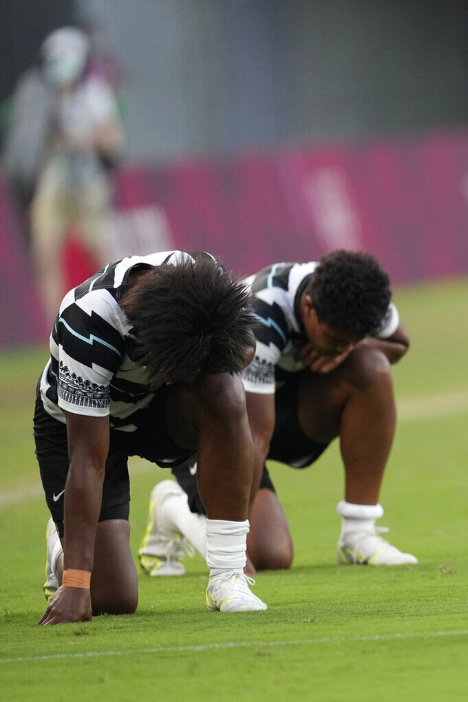 Fiji players kneel on the pitch after defeating Britain in the women's rugby bronze medal match at the 2020 Summer Olympics, Saturday, July 31, 2021 in Tokyo, Japan. (AP Photo/Shuji Kajiyama)
