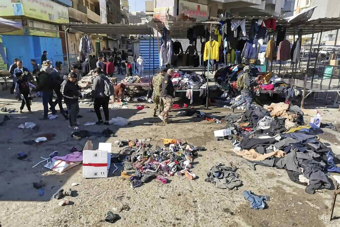 """FILE - In this Thursday, Jan. 21, 2021, file photo, people and security forces gather at the site of a deadly bomb attack in a market selling used clothes, in Baghdad, Iraq. The Islamic State group has claimed responsibility for a rare suicide attack that rocked central Baghdad, killing 32 people and wounding dozens. In a statement late Thursday, the group said the bombing """"targeted apostate Shiites."""" (AP Photo/Hadi Mizban, File)"""