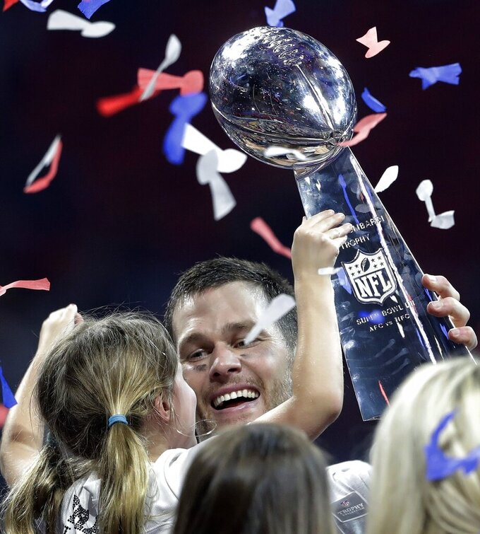 New England Patriots' Tom Brady holds the trophy and his daughter, Vivian, after the NFL Super Bowl 53 football game against the Los Angeles Rams, Sunday, Feb. 3, 2019, in Atlanta. The Patriots won 13-3. (AP Photo/John Bazemore)