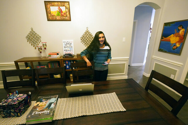 Charvi Goyal, 17, prepares to jump online for a tutoring session she gives to a junior high student from her family's home Monday, Jan. 4, 2021, in Plano, Texas. Goyal is part of a group of high school students that put together their own volunteer online tutoring service to help k-12 during the pandemic. (AP Photo/LM Otero)