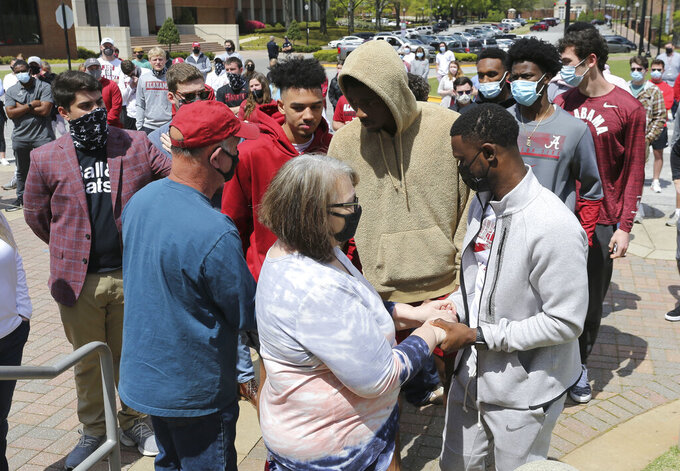 Alabama basketball players and coaches console Bryan and Pam Ratliff during a memorial for their son Luke Ratliff, on the steps of Coleman Coliseum on Saturday, April 3, 2021. From left are Jaden Shackelford, Herbert Jones and assistant coach Antoine Pettway. Health officials in Indiana said Saturday they are investigating whether anyone was exposed to COVID-19 by Alabama residents following Friday night's death of Luke Ratliff, a Crimson Tide fan who was in Indianapolis for the NCAA Tournament last weekend. Ratliff, a 23-year-old Alabama student, died after a brief illness, his father, Bryan Ratliff, told The Tuscaloosa News. The newspaper, citing multiple sources it did not identify, reported Ratliff died of complications related to COVID-19. (Gary Cosby Jr./The Tuscaloosa News via AP)