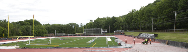Work crews spray on the synthetic surface while constructing the new track at Platt High School in Meriden, Conn., Tuesday, Jun3 2, 2020. (Dave Zajac/Record-Journal via AP)