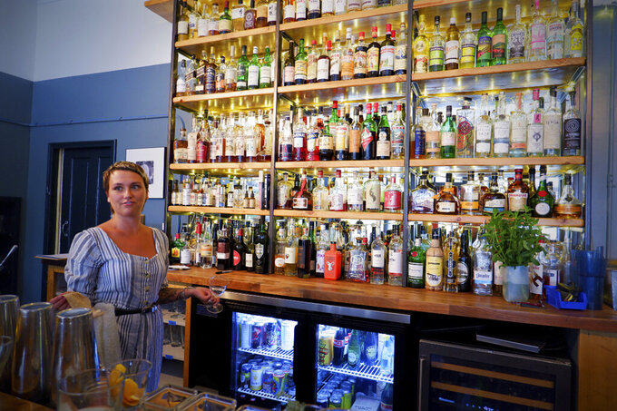 Bartender Mallory Zeller poses for a photo at Kerouac's restaurant Wednesday, June 23, 2021 in rural Baker, Nev. along the Utah line. The eatery is owned by a couple that gave up urban life in New York City back in 2017 to move to to the remote area near Great Basin National Park. (Ed Komenda/The Reno Gazette-Journal via AP)