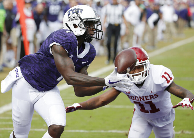 FILE - In this Oct. 20, 2018, file photo, TCU wide receiver Jalen Reagor (1) catches a pass in the end zone for a touchdown as Oklahoma cornerback Parnell Motley (11) defends during the first half of an NCAA college football game in Fort Worth, Texas. Reagor was selected by the Philadelphia Eagles in the first round of the NFL draft. (AP Photo/Brandon Wade, File)