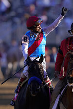 John Velazquez riding Medina Spirit acknowledges spectators after winning the 147th running of the Kentucky Derby at Churchill Downs, Saturday, May 1, 2021, in Louisville, Ky. (AP Photo/Michael Conroy)