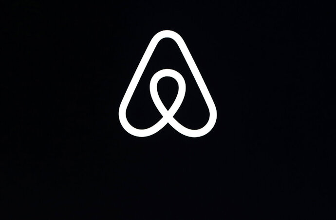 FILE - This Feb. 22, 2018, file photo, shows an Airbnb logo during an event in San Francisco. On Wednesday, Aug. 12, 2020, Airbnb announced that for the first time, it is taking legal action against a guest for violating its ban on unauthorized parties. (AP Photo/Eric Risberg, File)
