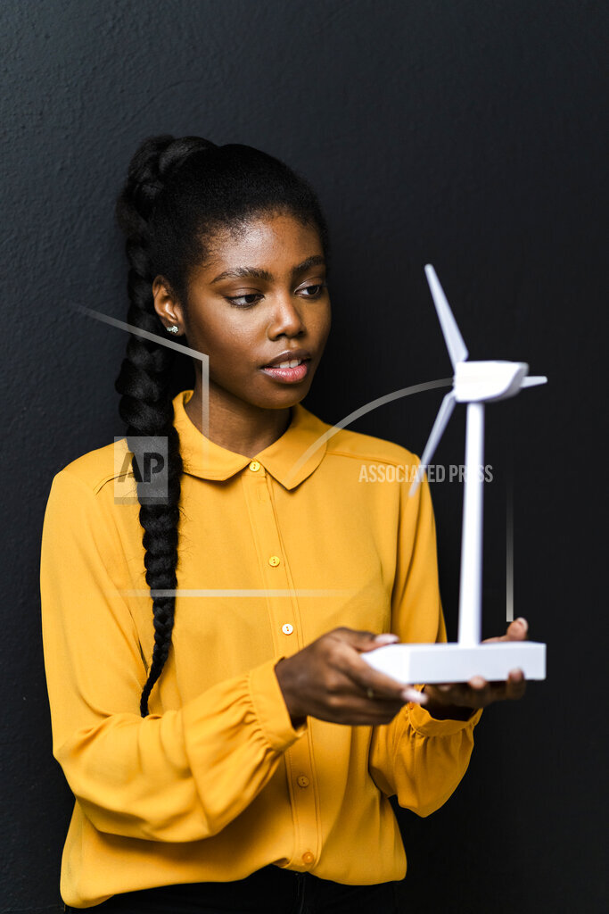 Businesswoman holding wind turbine model in front of black wall at studio