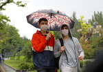 People wearing face masks for protection against the new coronavirus, walk in rain just hours before a four-day new curfew declared by the government in an attempt to control the spread of coronavirus, in Ankara, Turkey, Friday, May 22, 2020. The country has opted to impose short weekend and holiday curfews, instead of full lockdowns, fearing possible negative effects on the already troubled economy. (AP Photo/Burhan Ozbilici)