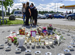 People gather near to where a twelve-year-old girl was shot and killed near a petrol station in Botkyrka, south of Stockholm, Sweden, Monday Aug. 3, 2020. (Stina Stjernkvist/TT via AP)