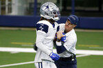 FILE - Dallas Cowboys special teams coordinator John Fassel tries to strip the ball out of the hands of wide receiver CeeDee Lamb (88) during an NFL football training camp in Arlington, Texas, Sunday, Aug. 30, 2020. Coaches around the NFL aren't quite sure what they'll get starting Thursday night when the 2020 season kicks off. The pandemic led to the league and players agreeing to limit potential exposure by wiping out all four preseason games, and that took away the ability to hone timing for special teams. (AP Photo/Michael Ainsworth, File)