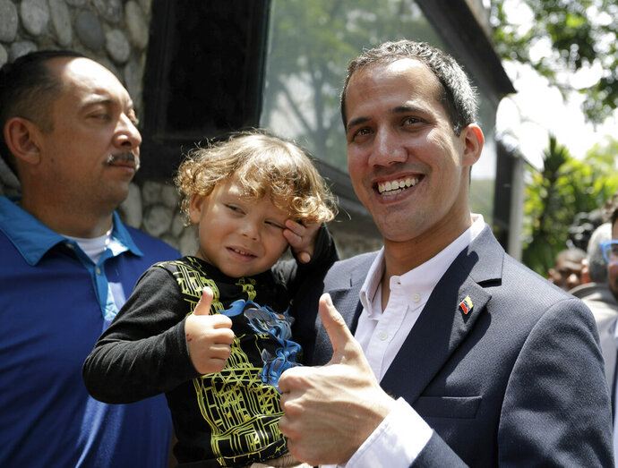 Opposition leader Juan Guaido, who has declared himself interim president of the country, flashes a thumbs up as he poses for a photo with a toddler, in Caracas, Venezuela, Thursday, March 21, 2019. Guaido says the Venezuelan government is weak and doesn't