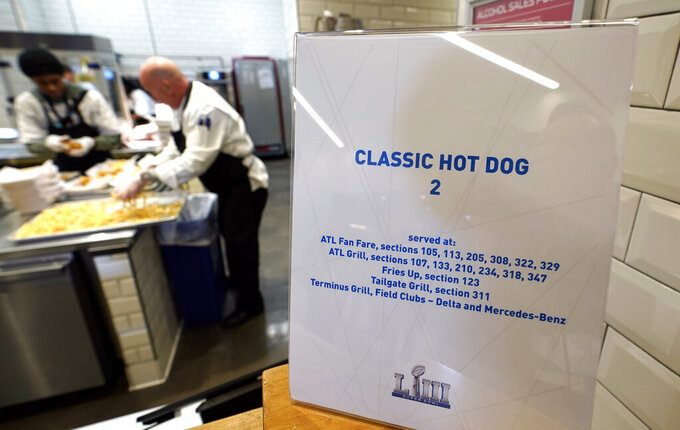 FILE - In this Jan. 29, 2019, file photo, workers prepare food for a media tasting event during a tour of Mercedes-Benz Stadium for the NFL Super Bowl 53 football game in Atlanta. (AP Photo/David J. Phillip, File)