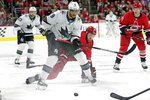 San Jose Sharks' Evander Kane (9) and Carolina Hurricanes' Jaccob Slavin (74) battle for the puck during the first period of an NHL hockey game in Raleigh, N.C., Thursday, Dec. 5, 2019. (AP Photo/Chris Seward)