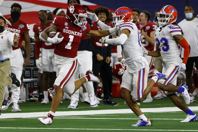 Oklahoma running back Seth McGowan (1) fights off a tackle attempt by Florida defensive back Donovan Stiner on a long gain during the second half of the Cotton Bowl NCAA college football game in Arlington, Texas, Wednesday, Dec. 30, 2020. (AP Photo/Ron Jenkins)
