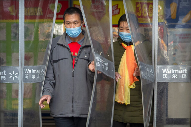 People wear face masks as they leave a Walmart grocery store in Beijing, Saturday, Feb. 1, 2020. China's death toll from a new virus rose to 259 on Saturday and a World Health Organization official said other governments need to prepare for