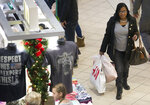 FILE - In this Tuesday, Dec. 26, 2017, file photo, Paulette Stone takes advantage of the post-Christmas sales at Valley View Mall in Roanoke, Va. The National Retail Federation said Friday, Jan. 12, 2018, that holiday sales reached $691.9 billion as shoppers stepped up their spending in the wake of a better economy. (Erica Yoon/The Roanoke Times via AP, File)