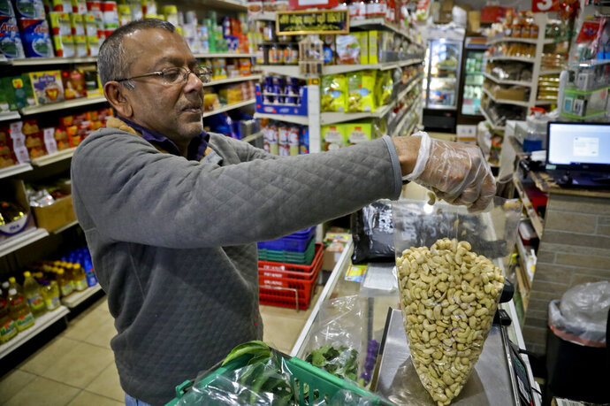 Dhannitha Meemanage, from Sri Lanka, bags cashews in his family's grocery store, in New York's Staten Island's