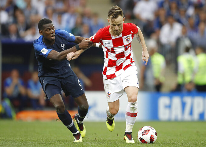 FILE - In this Sunday, July 15, 2018 file photo, France's Paul Pogba, pulls on the arm of Croatia's Ivan Rakitic during the final match between France and Croatia at the 2018 soccer World Cup in the Luzhniki Stadium in Moscow, Russia. Delaying the European Championship by a year has helped out some teams and hurt others. England had more time to integrate talented young players and deepen its squad. Croatia's squad from its run to the World Cup final in 2018 is nearing the end and Ivan Rakitic has retired from international soccer. (AP Photo/Francisco Seco, File)
