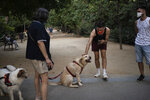 Piotr Grabarczyk, from Poland, pets a dog as he walks at a park with his boyfriend Kamil Pawlik, in Barcelona, Spain, Thursday, July 30, 2020. Grabarczyk and Pawlik are starting over in Spain, a country that — unlike Poland — allows same-sex couples the right to marry and adopt children. Like them, many LGBT people are choosing to leave Poland amid rising homophobia promoted by President Andrzej Duda and other right-wing populist politicians in power. (AP Photo/Felipe Dana)
