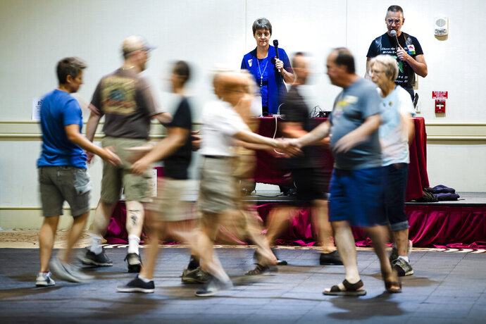 This July 3, 2019 photo shows Marge Coahran, left, of Toronto, and Scott Amspoker Albuquerque, N.M., calling to dancers during the annual International Association of Gay Square Dance Clubs convention in Philadelphia. The Independence Squares were founded 30 years ago in part as a social outlet for the LGBTQ community. (AP Photo/Matt Rourke)