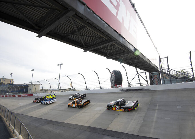Race trucks exit Turn 2 during a NASCAR Truck Series race at Dover International Speedway, Friday, Aug. 21, 2020, in Dover, Del. (AP Photo/Jason Minto)
