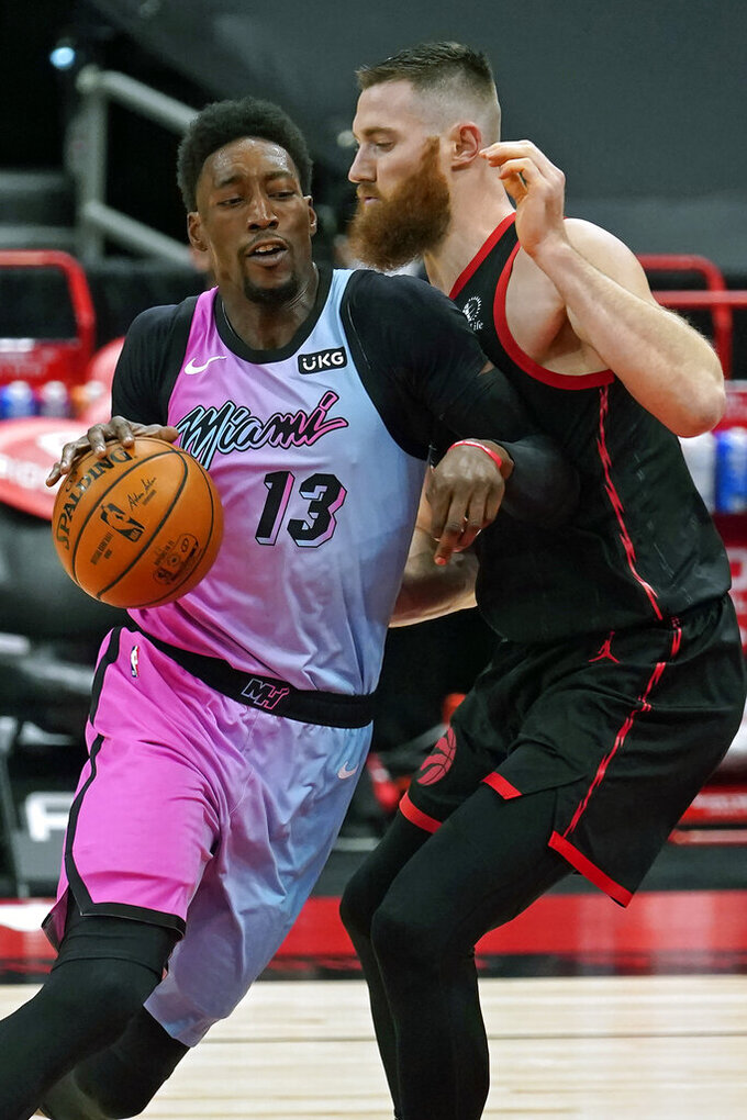 Miami Heat center Bam Adebayo (13) crashes into Toronto Raptors center Aron Baynes (46) during the first half of an NBA basketball game Wednesday, Jan. 20, 2021, in Tampa, Fla. (AP Photo/Chris O'Meara)