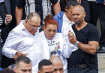 Miguel and Rosaly Rondon, parents of Leonel Rondon, 18, who died in the gas explosions in South Lawrence last week, watch as pall bearers carry their son's casket out of St. Mary the Assumption Parish in Lawrence, Mass., Wednesday, Sept. 19, 2018. (Amanda Sabga/The Eagle-Tribune via AP)