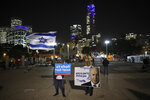 Israeli Prime Minister supporters stand during a support rally in Tel Aviv, Israel, Tuesday, Nov. 26, 2019. The sign with Hebrew reads: