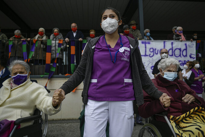 A health worker at San Jeronimo nursing home, wearing mask protection, holds hands with two elderly women while while taking part during International Women's Day in Estella, around 38 kms (23 miles) from Pamplona northern Spain, Monday, March 8, 2021. Many small-sized events are taking place across Spain creatively organized to prevent gatherings that could trigger a new spike of coronavirus contagion. (AP Photo/Alvaro Barrientos)