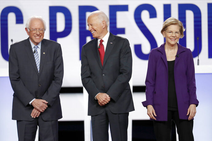Democratic presidential candidate Sen. Bernie Sanders, I-Vt., former Vice President Joe Biden, center, and Sen. Elizabeth Warren, D-Mass., right, stand on stage before a Democratic presidential primary debate hosted by CNN and The New York Times at Otterbein University, Tuesday, Oct. 15, 2019, in Westerville, Ohio. (AP Photo/John Minchillo)