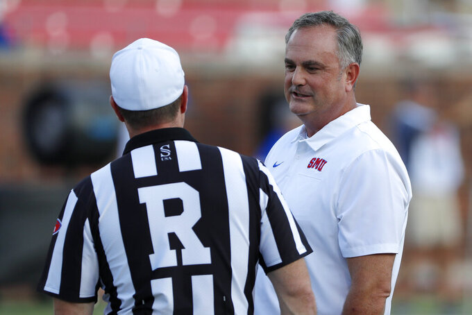 SMU head coach Sonny Dykes, right, talks with referee Edwin Lee, left, before an NCAA college football game against Tulsa, Saturday, Oct. 5, 2019, in Dallas, Texas. (AP Photo/Roger Steinman)