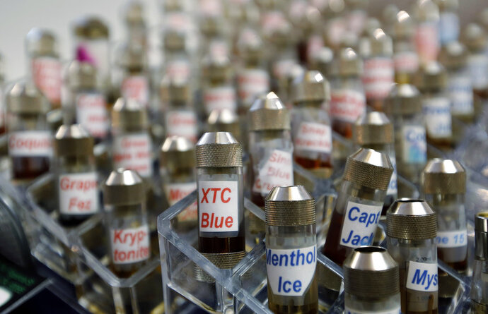 "FILE - This Dec. 4, 2013 file photo shows vials of flavored liquid at a store selling electronic cigarettes and related items in Los Angeles. On Wednesday, Sept. 12, 2018, U.S. health officials said teenage use of e-cigarette has reached ""epidemic"" levels in the U.S. and are calling on the industry to address the problem or risk having their flavored products pulled off the market. (AP Photo/Reed Saxon, File)"