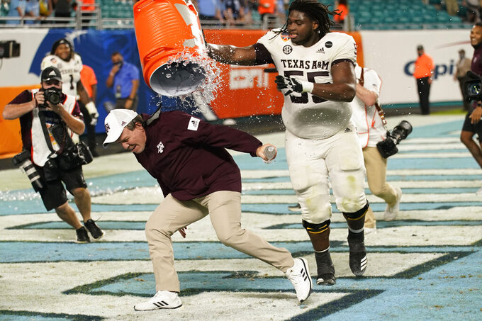 Texas A&M offensive lineman Kenyon Green (55) douses head coach Jimbo Fisher at the end of the Orange Bowl NCAA college football game, Saturday, Jan. 2, 2021, in Miami Gardens, Fla. Texas A&M defeated North Carolina 41-27. (AP Photo/Lynne Sladky)