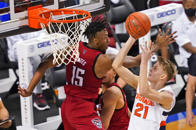 Syracuse forward Marek Dolezaj (21) goes up for a shot as North Carolina State forward Manny Bates (15) defends during the first half of an NCAA college basketball game in the second round of the Atlantic Coast Conference tournament in Greensboro, N.C., Wednesday, March 10, 2021. (AP Photo/Gerry Broome)