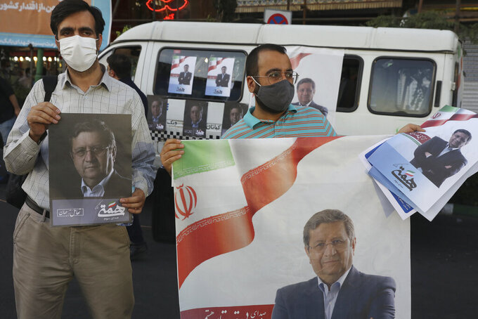 Supporters of Abdolnasser Hemmati, a presidential candidate in the June 18, elections, hold signs with his picture, during a street rally in Tehran, Iran, Tuesday, June 15, 2021. Hemmati, a prominent contender in Iran's presidential election appealed Tuesday for better economic and political relations with the West, his most extensive attempt yet to attract reformist voters just days ahead of the poll. (AP Photo/Vahid Salemi)