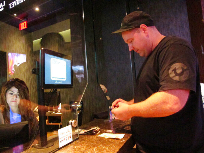 In this Sept. 4, 2019 photo, Gary Kosakowski of Newark, N.J. places a bet on the New York Mets at the sports book in the Borgata casino in Atlantic City, N.J. As the second NFL season begins following a U.S. Supreme Court decision clearing the way for legal sports betting, the industry is growing larger and ever-more mobile in the U.S. (AP Photo/Wayne Parry)